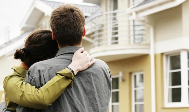 young couple in front of a tan home with white accents